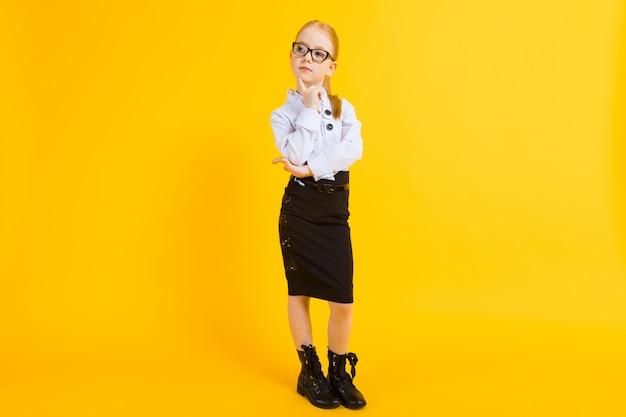 Retrato de una hermosa niña en una blusa blanca y falda negra.