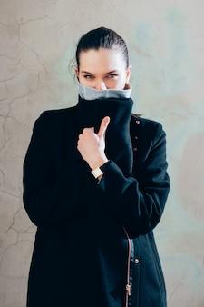 Retrato de una hermosa niña con cabello castaño en un abrigo negro