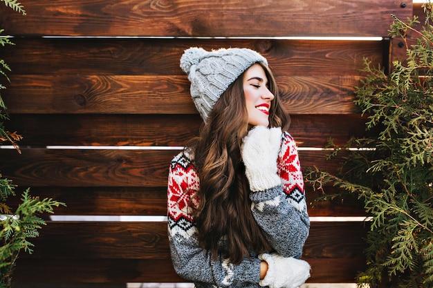Retrato hermosa niña con cabello largo y labios rojos en ropa de invierno abrigada en madera. ella sonríe a un lado y mantiene los ojos cerrados.
