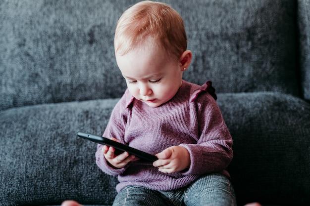 Retrato de hermosa niña en casa sentado en el sofá con teléfono móvil