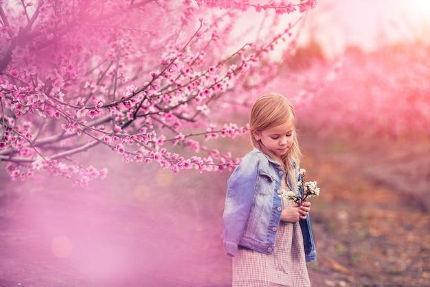 Retrato de una hermosa niña cerca de un árbol floreciente de almendras y lilas