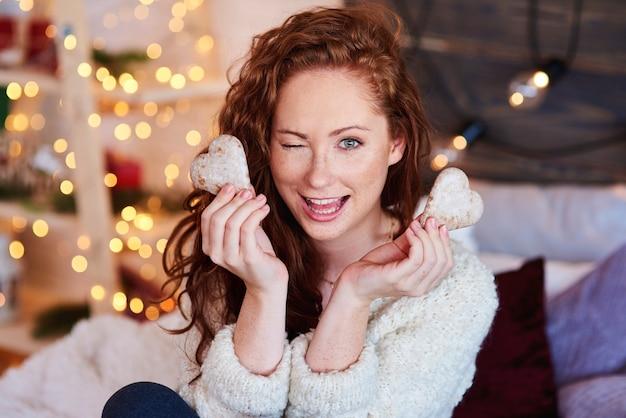 Retrato de hermosa niña divirtiéndose con galleta de jengibre