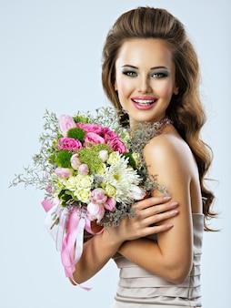 Retrato de hermosa niña feliz con flores en las manos. mujer atractiva joven sostiene el ramo de flores de primavera