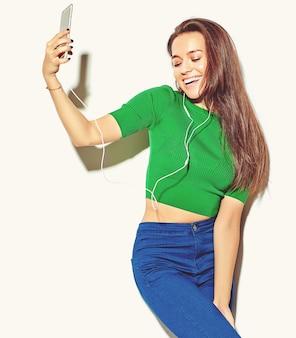 Retrato de hermosa niña feliz linda morena sonriente mujer en ropa de verano casual hipster verde sin maquillaje aislado en blanco, tomar una selfie