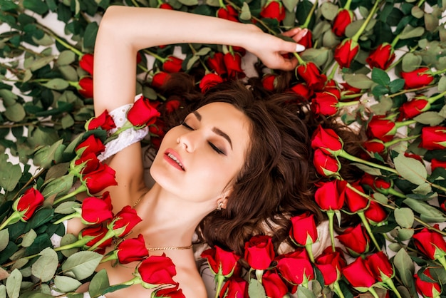 Retrato de una hermosa niña con flores rojas y rosas. primer de la cara de la mujer del modelo de alta moda de la belleza. piel perfecta. maquillaje profesional. formar. lápiz labial, fundación, anuncios de rímel.