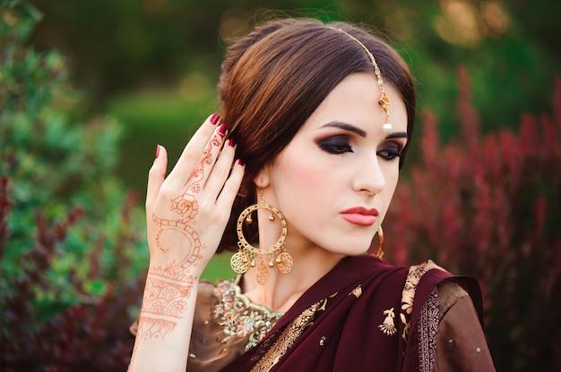 Retrato de hermosa niña india. modelo joven hindú con tatoo mehndi y joyería kundan. sari tradicional traje indio.