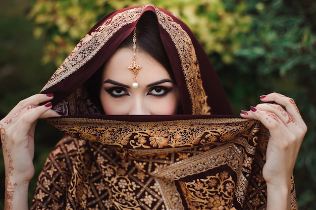 Retrato de hermosa niña india. modelo joven hindú con tatoo mehndi y joyería kundan.