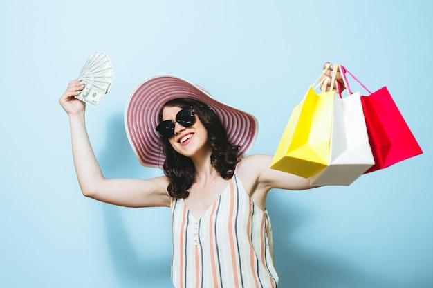 Retrato de una hermosa niña morena feliz aislada sobre fondo azul con billetes de dinero y bolsa de compras
