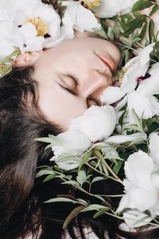 Retrato de una hermosa niña morena con flores blancas y púrpuras. hermosa morena joven disfrutando de flores. idea de portada humor