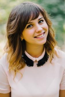 Retrato de hermosa niña morena sonriente en otoño