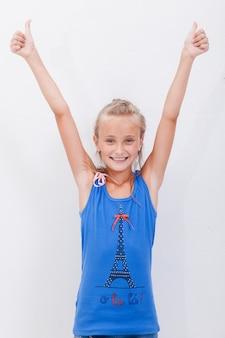 Retrato de una hermosa niña mostrando los pulgares para arriba