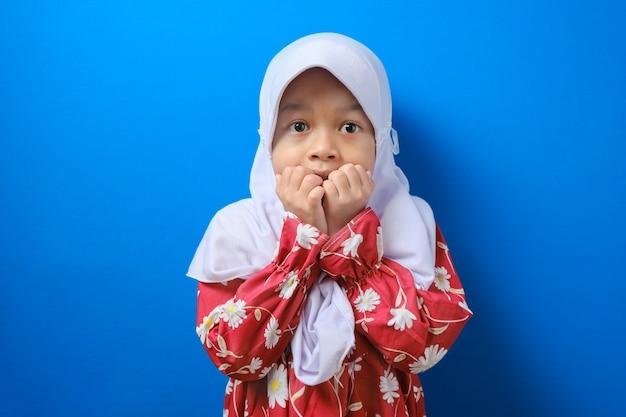 Retrato de hermosa niña musulmana asiática vistiendo hijab sorprendido mientras se muerde la uña sobre fondo azul.