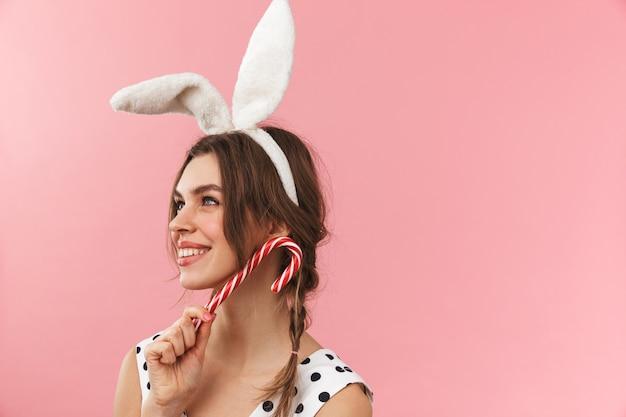 Retrato de una hermosa niña con orejas de conejo que se encuentran aisladas, haciendo muecas, sosteniendo bastón de caramelo