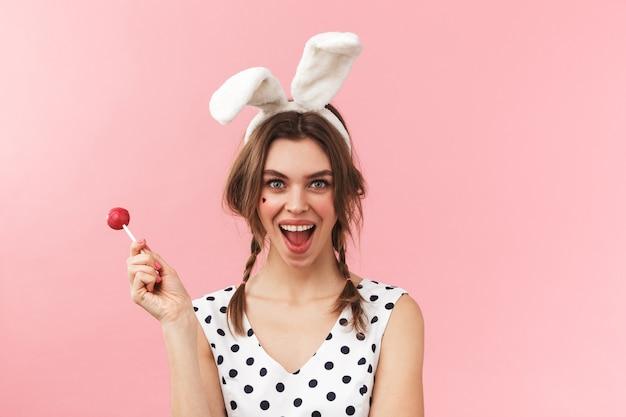 Retrato de una hermosa niña con orejas de conejo que se encuentran aisladas, haciendo muecas, sosteniendo lollipop