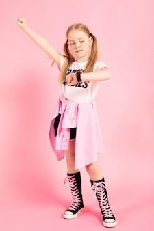 Retrato de una hermosa niña en pantalones cortos, una camiseta y zapatillas altas.