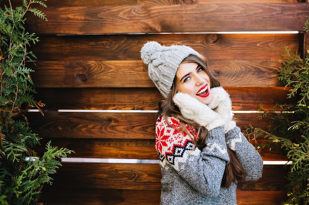 Retrato hermosa niña con pelo largo en sombrero de punto y suéter de invierno en madera. ella toca la cara con las manos en guantes y sonríe.