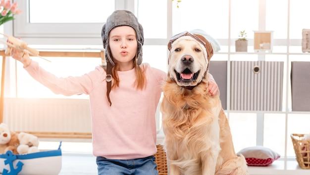 Retrato de hermosa niña y perro golden retriever con sombrero y gafas de piloto especiales