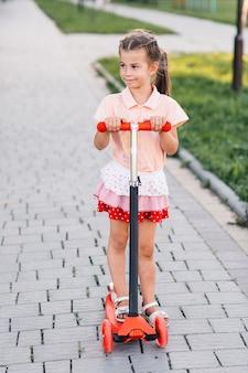 Retrato de una hermosa niña de pie en patinete scooter en el parque