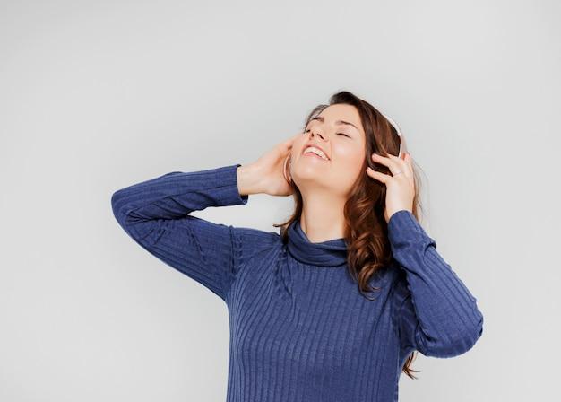 Retrato de hermosa niña positiva en auriculares disfrutando de la música