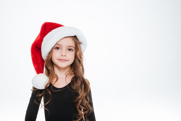 Retrato de hermosa niña rizada con sombrero de santa claus