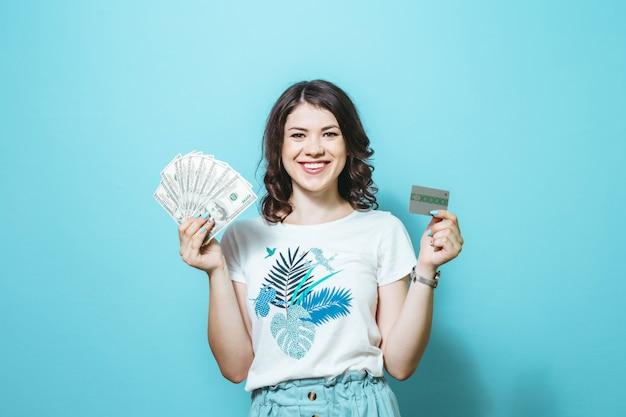 Retrato de una hermosa niña satisfecha con billetes de dinero y tarjeta de crédito aislado sobre fondo azul.