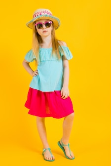Retrato de una hermosa niña en un sombrero, gafas de sol, vestido de verano y sandalias.