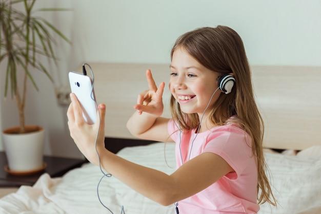 Retrato de hermosa niña sonriendo en smartphone, tomando selfie