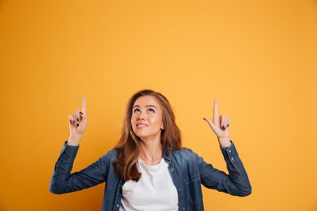 Retrato de una hermosa niña sonriente apuntando dos dedos hacia arriba