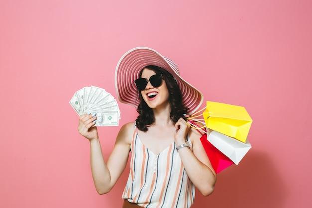 Retrato de una hermosa niña sonriente con gafas de sol, sosteniendo bolsas de compra y billetes de dinero sobre fondo rosa