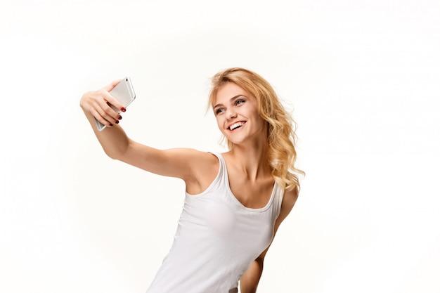 Retrato de hermosa niña sonriente con teléfono moderno