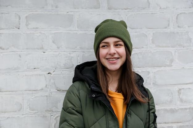 Retrato de una hermosa niña sonriente con tirantes en un suéter amarillo y sombrero de color caqui, que se encuentra cerca de una pared de ladrillo blanco. el concepto de emociones y espacio de copia.