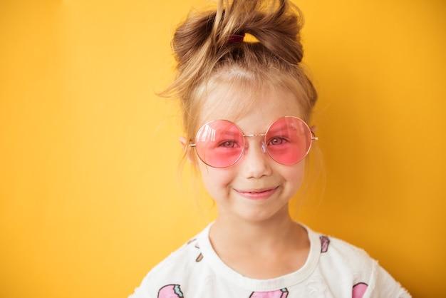 Retrato de una hermosa niña sonriente en vasos con gafas de color rosa sobre un fondo amarillo