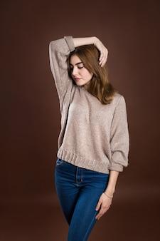 Retrato de una hermosa niña en un suéter sobre un fondo marrón