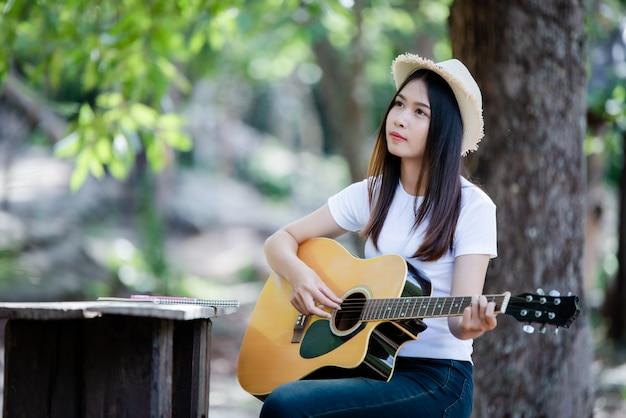Retrato de una hermosa niña tocando la guitarra con la escritura en la naturaleza