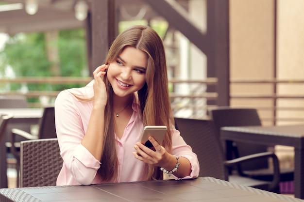Retrato de hermosa niña usando su teléfono móvil en la cafetería