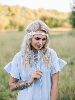 Retrato de una hermosa niña con un vestido azul en un campo al atardecer en verano.