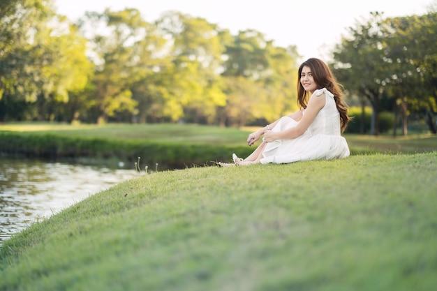 Retrato de una hermosa niña de vestido blanco, sentada en el campo de hierba al lado del río