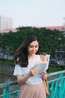 Retrato de hermosa niña vietnamita de pie y leyendo un libro en el viento con desenfoque de fondo de la ciudad. lector feliz en la universidad.