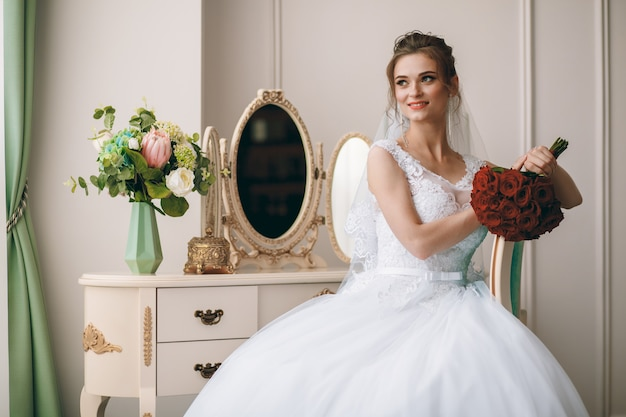 Retrato de la hermosa novia en bata de seda blanca con peinado rizado y velo largo sentado cerca de la ventana en el dormitorio, espacio de copia.