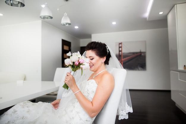 Retrato de hermosa novia feliz sentada en el sofá