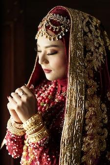 Retrato de una hermosa novia india en vestido rojo y dorado