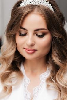 Retrato de una hermosa novia niña feliz con maquillaje y peinado en la mañana del día de la boda