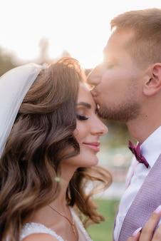 Retrato de la hermosa novia y el novio caucásico al aire libre con los ojos cerrados, besándose