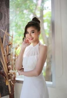 Retrato de hermosa novia en vestido de novia con falda larga y larga, la novia en el parque es un hermoso vestido de novia largo.