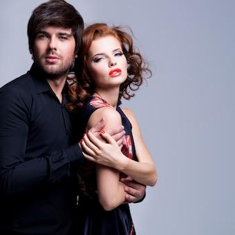 Retrato de hermosa pareja apasionada enamorada abrazado sobre fondo gris.