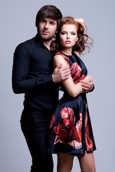 Retrato de hermosa pareja apasionada enamorada abrazado sobre fondo gris