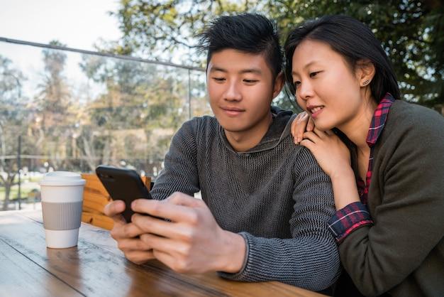 Retrato de hermosa pareja asiática mirando el teléfono móvil mientras está sentado y pasar tiempo en la cafetería.