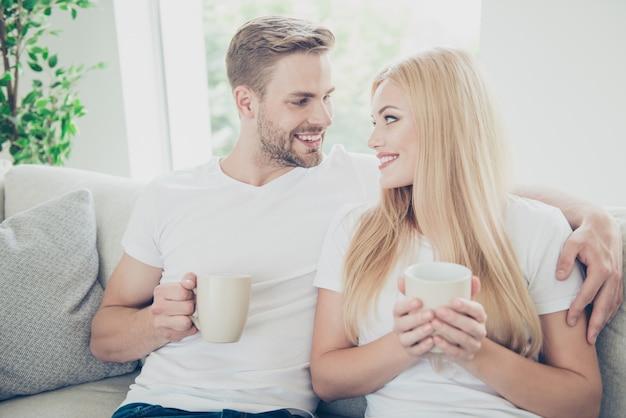 Retrato de hermosa pareja en camisetas blancas en casa tomando café