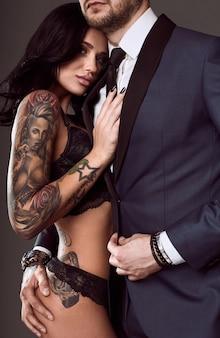 Retrato de una hermosa pareja: hombre brutal en traje elegante y chica sexy con un tatuaje en lencería sobre fondo gris
