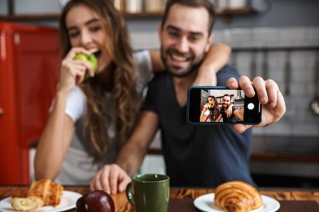 Retrato de hermosa pareja hombre y mujer tomando foto selfie en teléfono celular mientras desayuna en la cocina de casa
